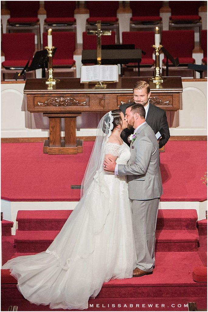 bride and groom first kiss at altar Mt Horeb UMC Lexington SC wedding photographer in Columbia SC