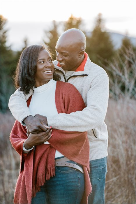 black couple laughing on mountain top greenville sc engagement photography