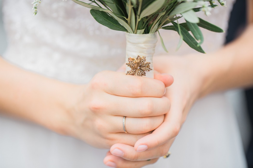 Bride's hands holding bouquet with grandmother's brooch in Cortona Italy Tuscany wedding photography Melissa Brewer Photography fine art film wedding photographer in Italy