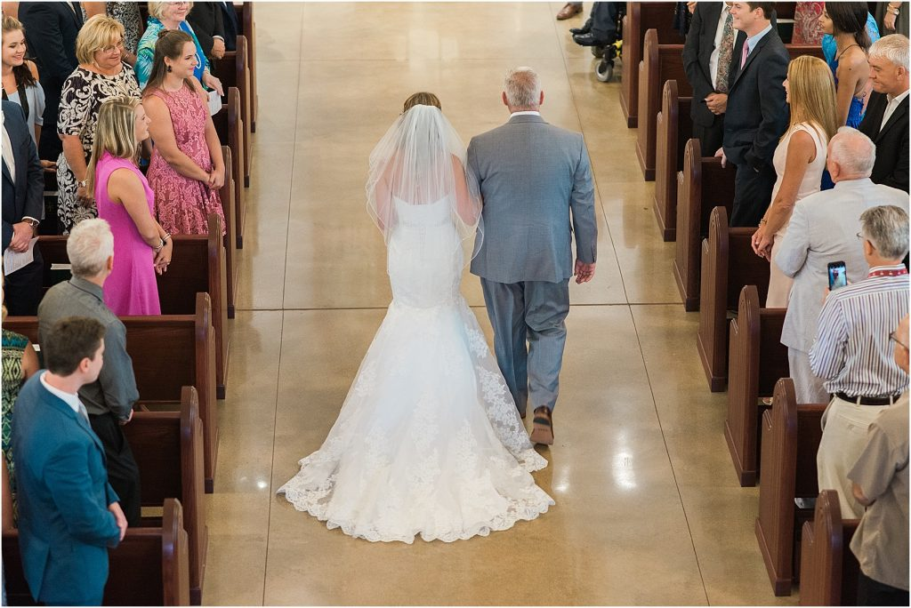 father walks his daughter down the aisle at our lady of the lake catholic church wedding