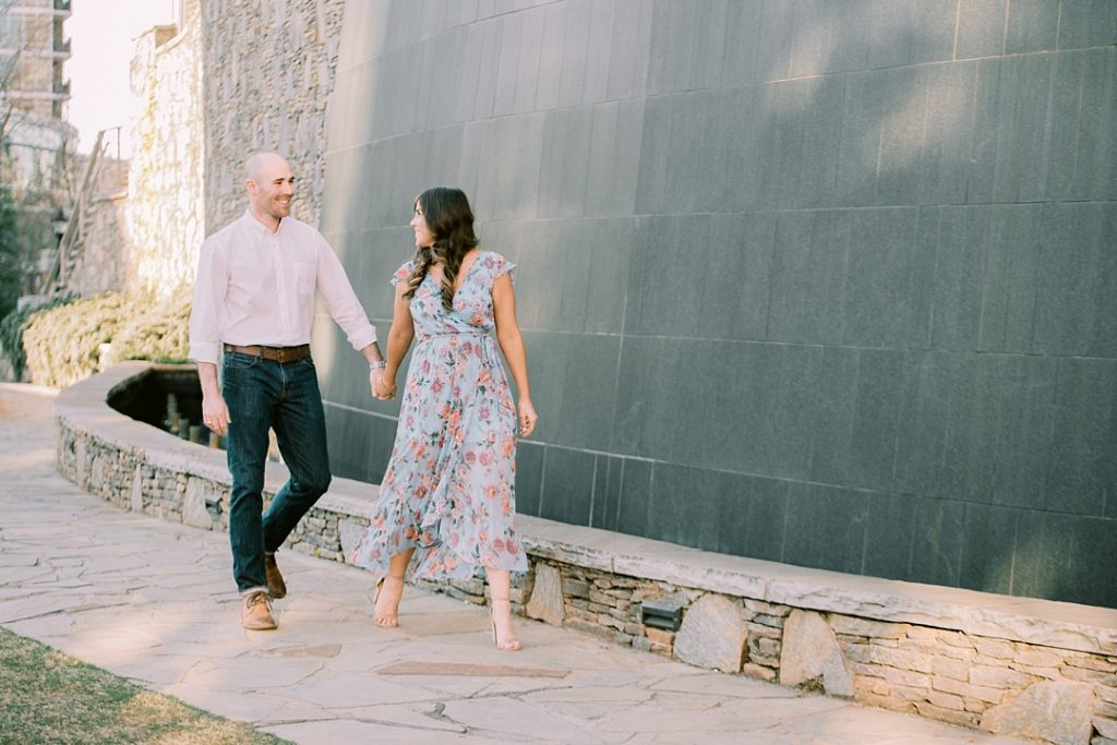 waterfall at peace center greenville sc lovers holding hands and walking engagement session in greenville sc melissa brewer photography