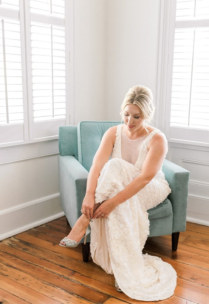 bride putting on shoes in amazing light charleston film photography