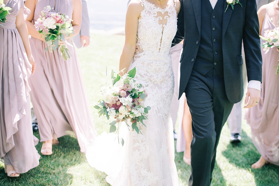 bride and groom walking at cliffs at glassy chapel brunch wedding with wedding party bridesmaids groomsmen purple bridal bouquet film photography