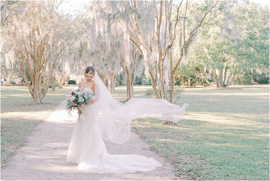 bride with veil blowing in the wind hampton park charleston sc spanish moss row wedding