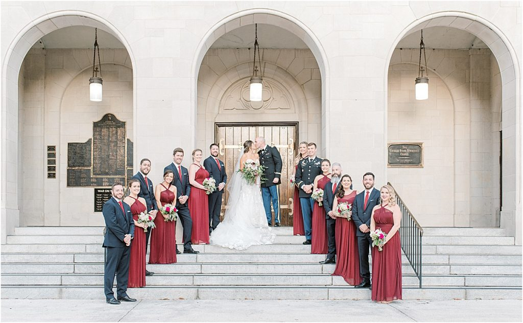 full wedding party standing on the steps at citadel's summerall chapel red bridesmaids navy groomsmen